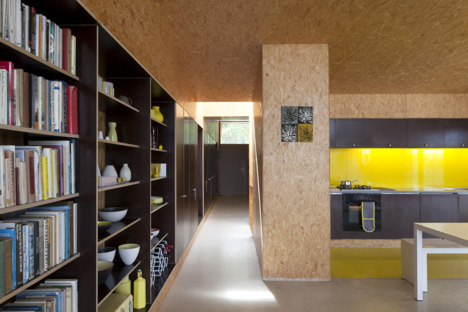 The open-plan space with a long wall of shelves and cupboards