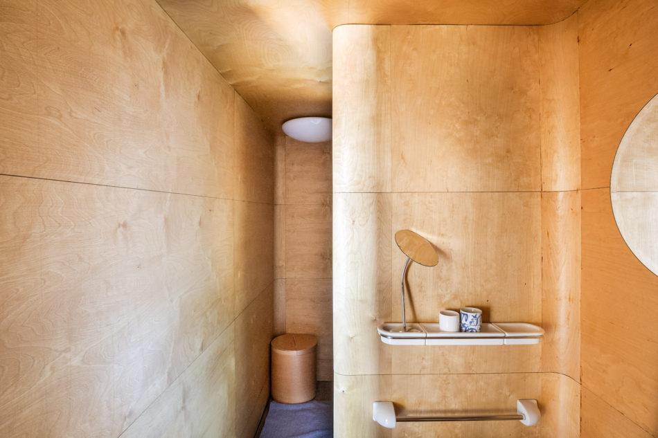 the bent plywood-clad bathroom
